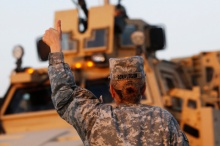 U.S. Army convoys are given the thumbs up from a fellow soldier after crossing into Kuwait during the last convoy out of Iraq