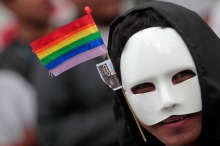A masked member of the LGBT community, bearing the rainbow flag, looks on during the XII Parade of Sexual Diversity in Guatemala City
