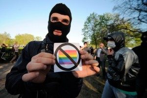 An-anti-gay-rights-activist-shows-a-badge-during-a-flash-mob-organized-by-gay-rights-protesters-in-St.Petersburg-Russia-on-May-17-2012.-Valentina-SvistunovaInterpressReuters-650x432