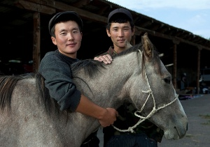 Two Young Men Holding A Horse At The Animal Market Of Kochkor, Kyrgyzstan